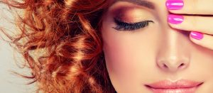 redhead woman with curls and pink nails