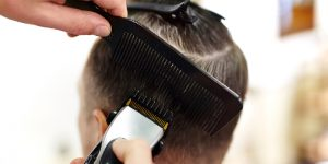 barber cutting hair with electric trimmer