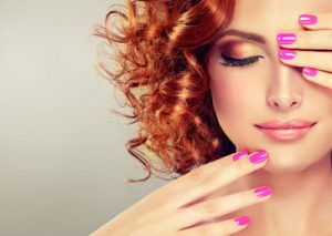 redhead woman with curly hair and pink fingernails