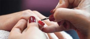 nail technician painting fingernails red