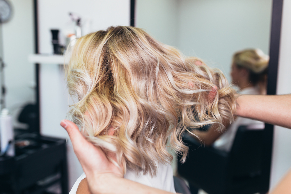 woman's blond hair being fanned out by hair stylist's hands