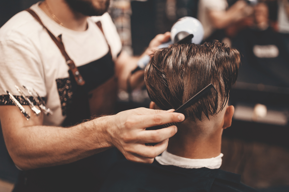 barber holds back man's hair before trimming