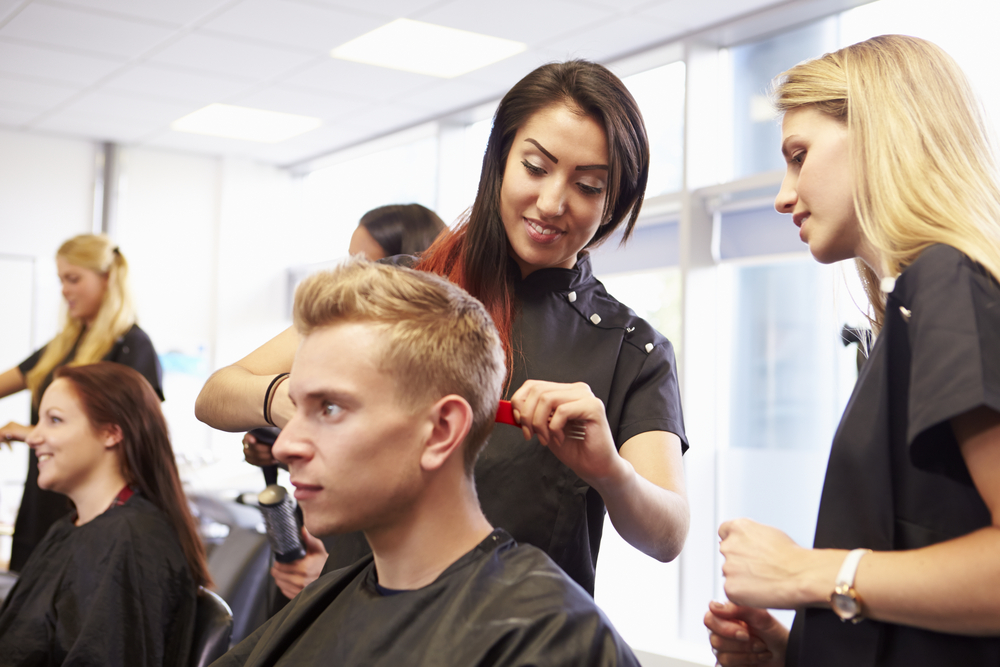 man gets hair trimmed by two cosmetologists in training