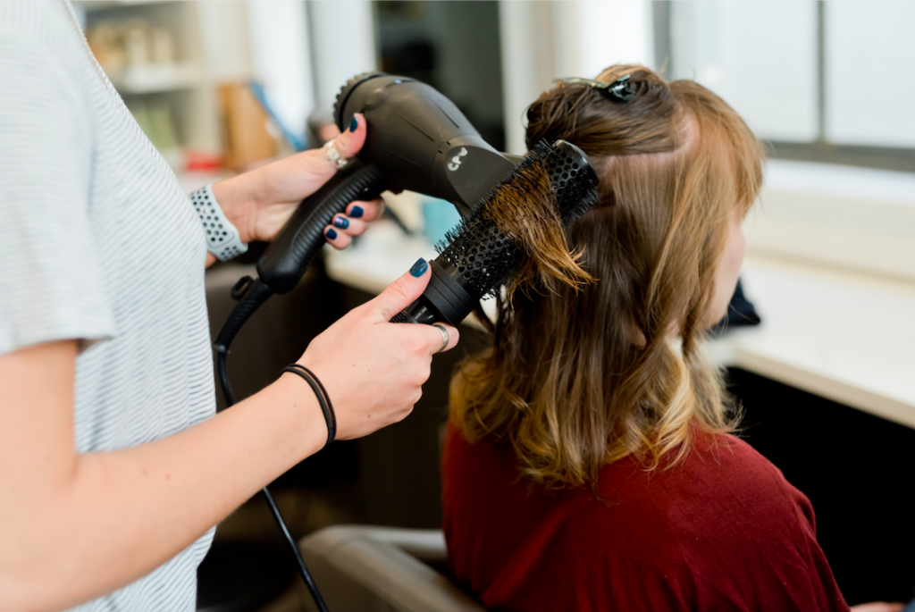 woman having her hair blow dried at a salon